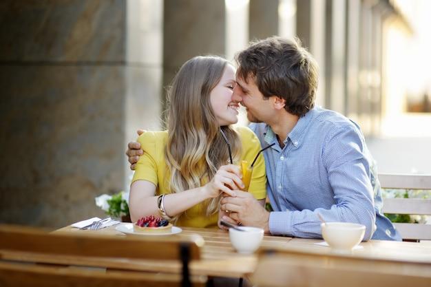 Młoda para po śniadaniu w kawiarni na świeżym powietrzu