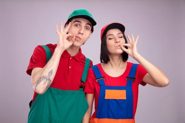 Młoda para pod wrażeniem faceta zadowolona dziewczyna w mundurze pracownika budowlanego i czapce facet zapinający usta gestem dziewczyna robi pyszny gest z zamkniętymi oczami