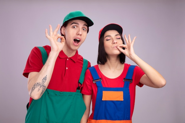 Młoda para pod wrażeniem faceta zadowolona dziewczyna w mundurze pracownika budowlanego i facet w czapce robi ok znak dziewczyna robi pyszny gest z zamkniętymi oczami