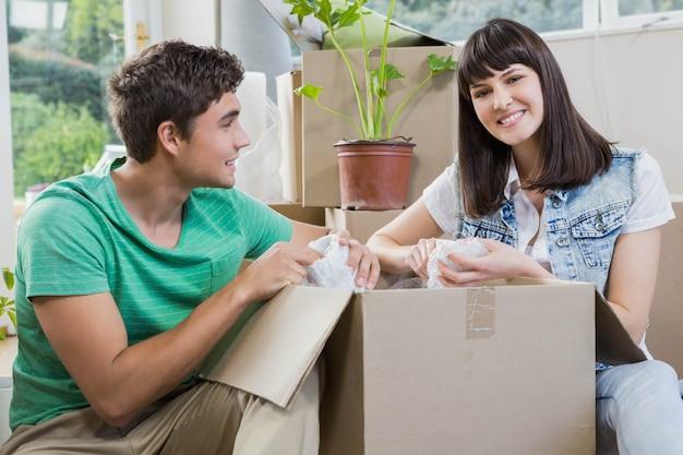 Młoda para pomaga sobie nawzajem podczas rozpakowywania kartonów w nowym domu