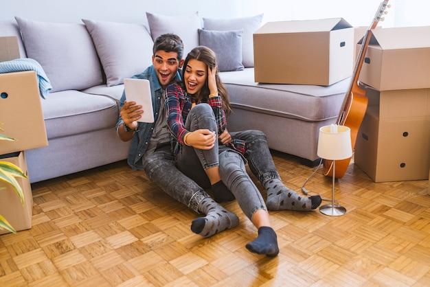 Młoda para porusza się w nowym domu. siedzenie na podłodze i relaks po oczyszczeniu i rozpakowaniu.