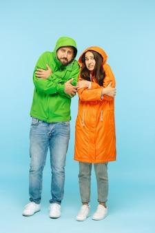 Młoda para pozowanie studio w jesiennej kurtce na białym tle na niebiesko. ludzkie negatywne emocje. pojęcie zimnej pogody. koncepcje mody męskiej i żeńskiej