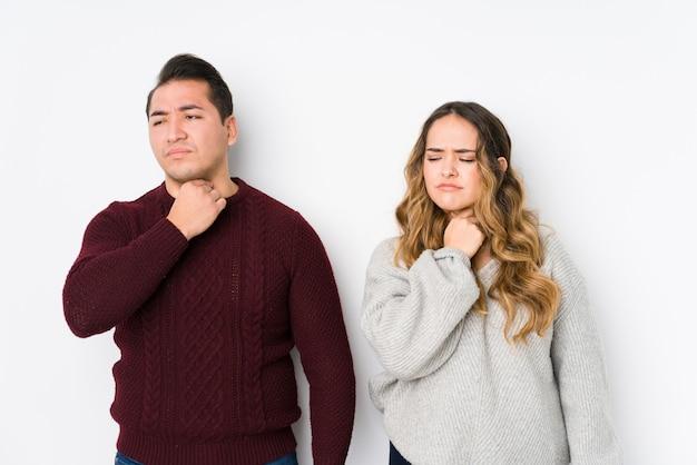 Młoda para pozuje w białej ścianie cierpi na ból gardła z powodu wirusa lub infekcji.