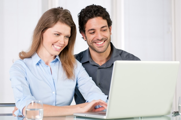 Młoda para pracuje razem na komputerze przenośnym w domu