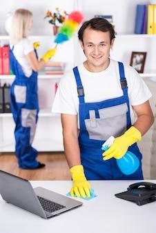 Młoda para profesjonalnych sprzątaczy sprząta biuro.