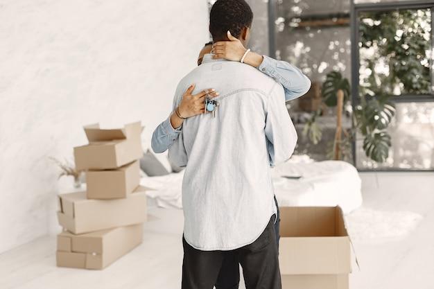 Młoda para przeprowadza się razem do nowego domu. afroamerykanin para z kartonów. kobieta trzyma klucze.
