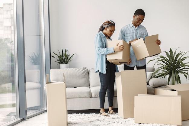 Młoda para przeprowadza się razem do nowego domu. afroamerykanin para z kartonów.