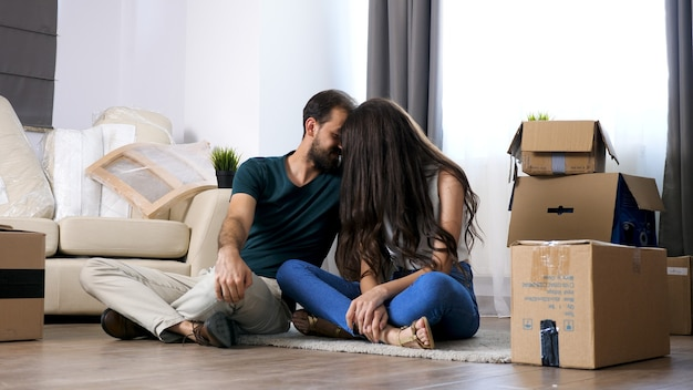 Młoda para przeprowadza się w nowym domu. siedzi na podłodze i relaksuje się po rozpakowaniu