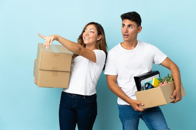 Młoda para przeprowadza się w nowym domu wśród pól na niebiesko, wskazując na bok, aby przedstawić produkt