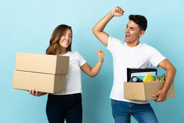 Młoda para przeprowadza się w nowym domu wśród pudeł na niebiesko świętuje zwycięstwo w pozycji zwycięzcy