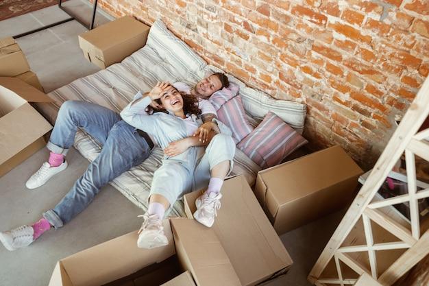 Młoda para przeprowadziła się do nowego domu lub mieszkania. leżąc razem, relaksując się po sprzątaniu i rozpakowaniu w dniu przeprowadzki. wyglądaj szczęśliwie, rozmarzonym i pewnym siebie. rodzina, przeprowadzka, relacje, pierwsza koncepcja domu.
