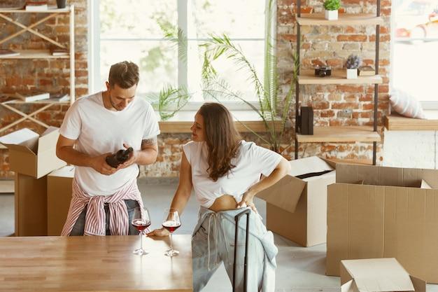 Młoda para przeprowadziła się do nowego domu lub mieszkania. picie czerwonego wina, uśmiechanie się i relaks po czyszczeniu i rozpakowaniu. wyglądaj na szczęśliwego i pewnego siebie. rodzina, przeprowadzka, relacje, pierwsza koncepcja domu.