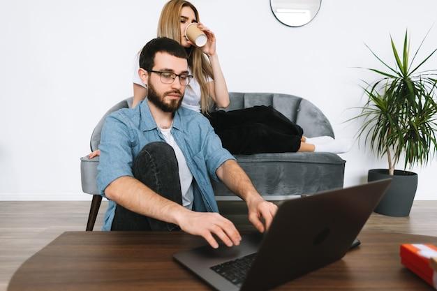 Młoda para przy użyciu komputera przenośnego, przeglądania informacji i patrząc na ekran laptopa w nowoczesnym salonie na kanapie.