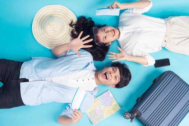 Młoda para przygotowuje się do podróży na niebieskim tle