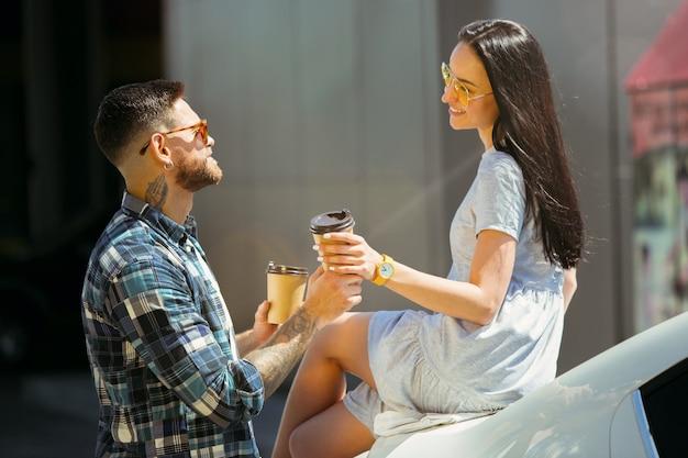 Młoda para przygotowuje się do wakacyjnej podróży samochodem w słoneczny dzień. kobieta i mężczyzna pije kawę i gotowe do wyjścia w morze lub ocean.