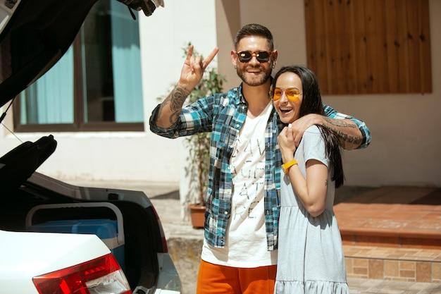 Młoda para przygotowuje się do wakacyjnej podróży samochodem w słoneczny dzień. kobieta i mężczyzna przytulanie i uśmiechanie się. gotowy do wyjścia w morze, nad rzekę lub ocean. pojęcie związku, lato, weekend.