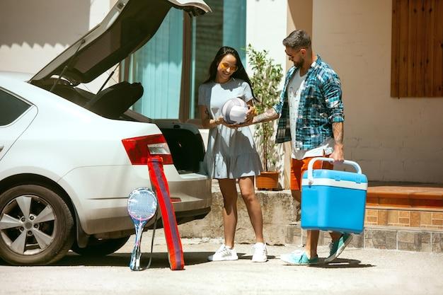 Młoda para przygotowuje się do wakacyjnej podróży samochodem w słoneczny dzień. kobieta i mężczyzna układanie sprzętu sportowego. gotowy do wyjścia w morze, nad rzekę lub ocean. pojęcie związku, lato, weekend.