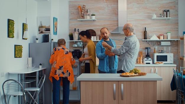 Młoda para przynosząca zakupy ze sklepu. mąż i żona przychodzą z zakupów przynosząc papierową torbę z zakupami, świeże jedzenie z supermarketu w domu rodziców, aby przygotować rodzinny obiad