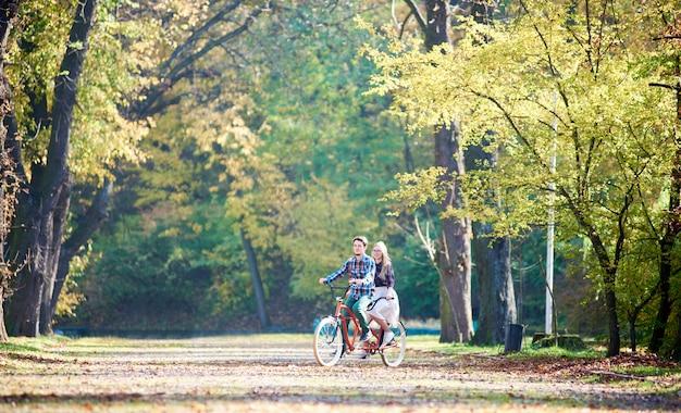 Młoda para, przystojny mężczyzna i atrakcyjna kobieta na rowerze tandemowym w słoneczny letni park lub las.