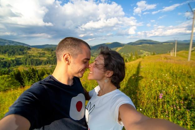 Młoda para przytula się i robi selfie z niesamowitym górskim krajobrazem.