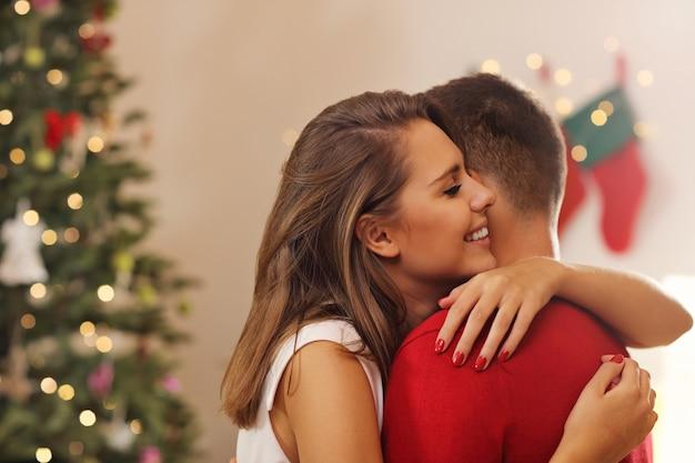 Młoda para przytulająca się nad choinką