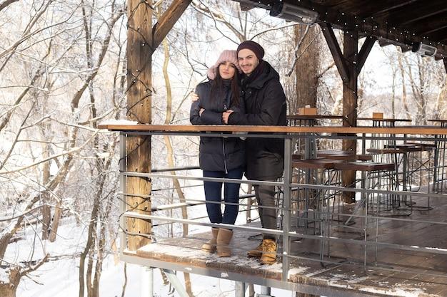 Młoda para przytulanie i całowanie w parku w zimowej kawiarni