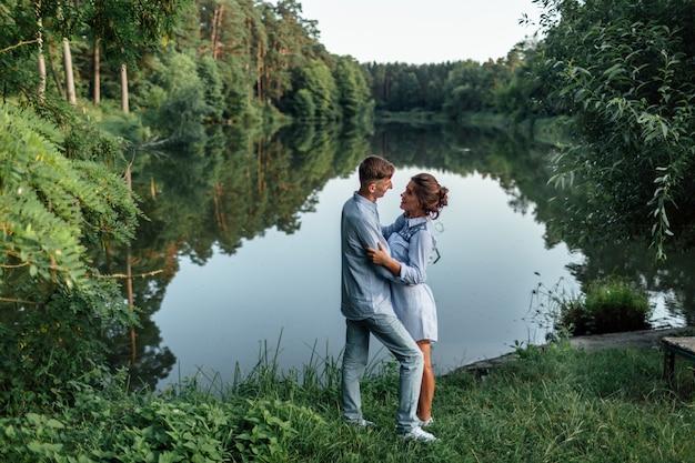 Młoda para przytulanie i spacer w pobliżu jeziora w słoneczny dzień.