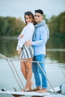 Młoda para przytulanie na pokładzie żaglówki. romantyczna para na statku wycieczkowym. szczęśliwy zamożny mężczyzna i kobieta prywatną łodzią mają wycieczkę morską. para na miesiąc miodowy podróżująca jachtem