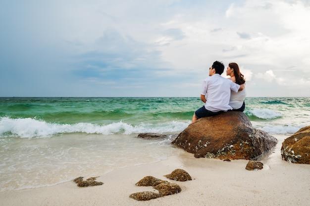 Młoda para przytulanie na skale plaży na wyspie koh munnork, rayong, tajlandia