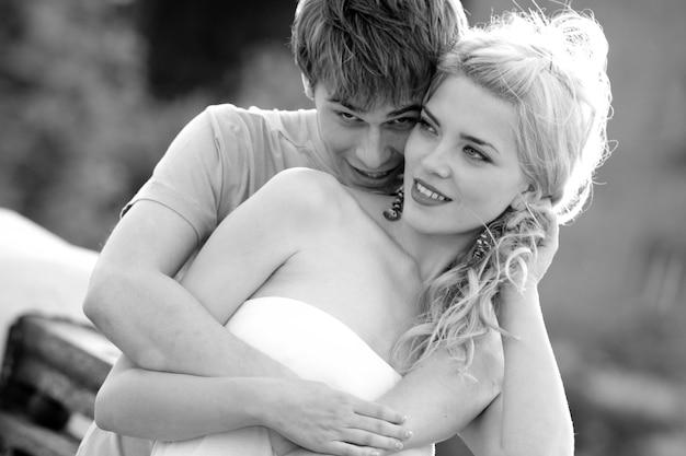 Młoda para przytulanie podczas spaceru na moście słoneczny słoneczny letni dzień. pojęcie miłości, romansu i wierności