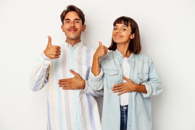 Młoda para rasy mieszanej na białym tle dotyka brzucha, delikatnie się uśmiecha, koncepcja jedzenia i satysfakcji.