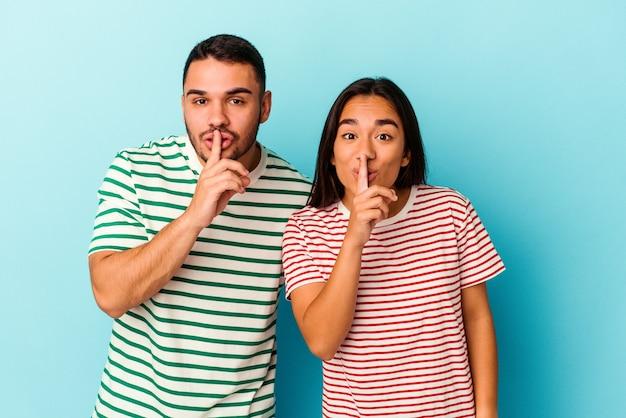Młoda para rasy mieszanej na białym tle na niebieskim tle zachowując tajemnicę lub prosząc o ciszę.