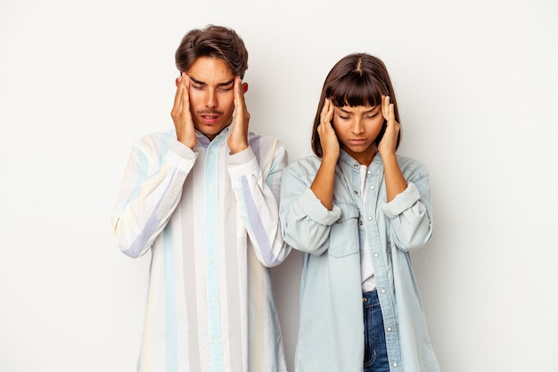 Młoda para rasy mieszanej na białym tle o ból głowy, dotykając przodu twarzy.