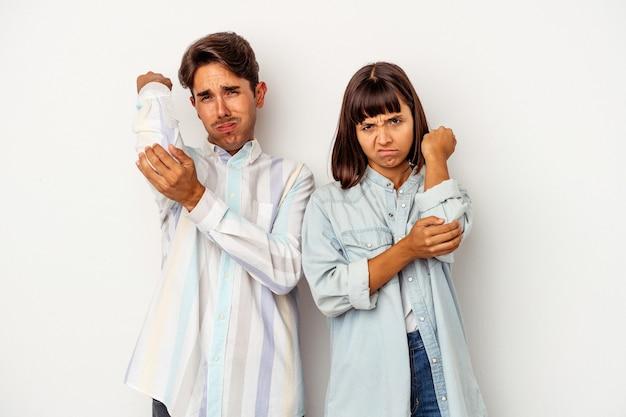 Młoda para rasy mieszanej na białym tle o ból szyi z powodu stresu, masowania i dotykania go ręką.