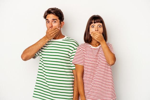 Młoda para rasy mieszanej na białym tle obejmujące usta rękami patrząc zmartwiony.