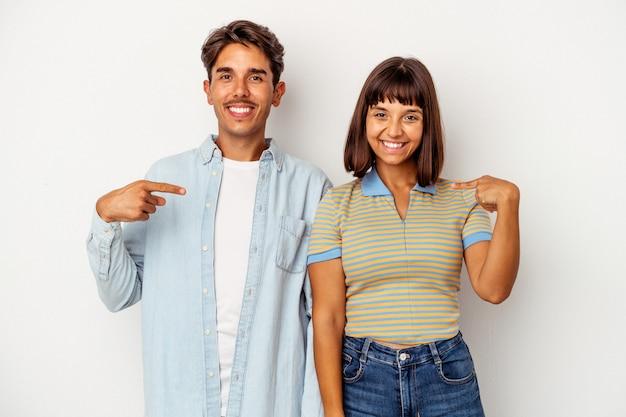 Młoda para rasy mieszanej na białym tle osoba wskazująca ręcznie na miejsce na koszulkę, dumna i pewna siebie