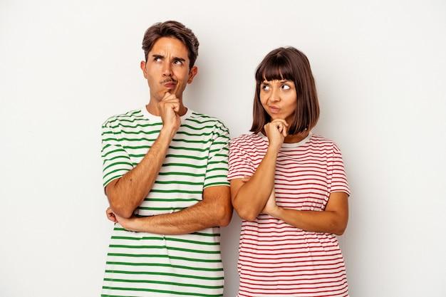 Młoda para rasy mieszanej na białym tle patrząc w bok z wyrazem wątpliwości i sceptyczny.