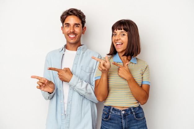 Młoda para rasy mieszanej na białym tle podekscytowany, wskazując z dala od palców wskazujących.