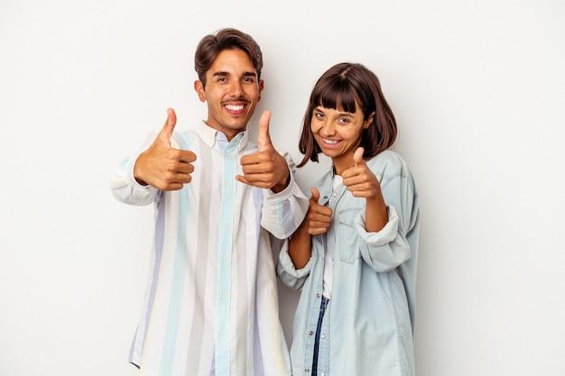 Młoda para rasy mieszanej na białym tle podnosząc oba kciuki do góry, uśmiechnięta i pewna siebie.