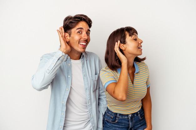 Młoda para rasy mieszanej na białym tle próbuje słuchać plotek.