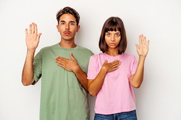 Młoda para rasy mieszanej na białym tle składając przysięgę, kładąc rękę na klatce piersiowej.