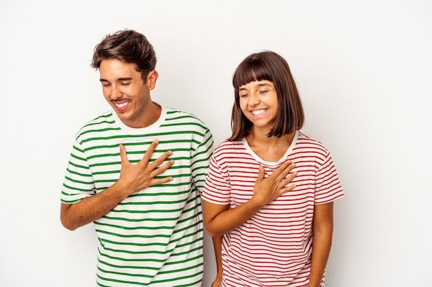 Młoda para rasy mieszanej na białym tle śmiejąc się trzymając ręce na sercu, pojęcie szczęścia.