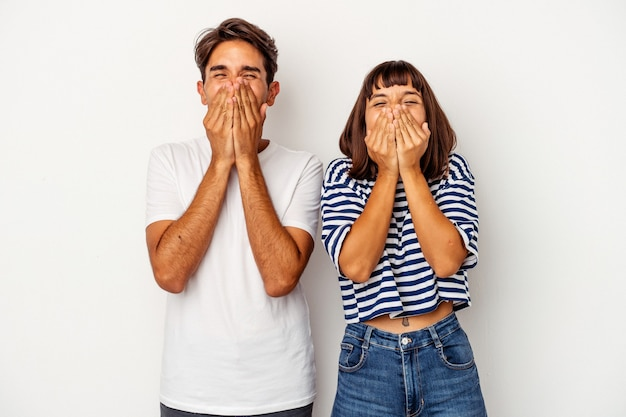 Młoda para rasy mieszanej na białym tle śmiejąc się z czegoś, zakrywając usta rękami.