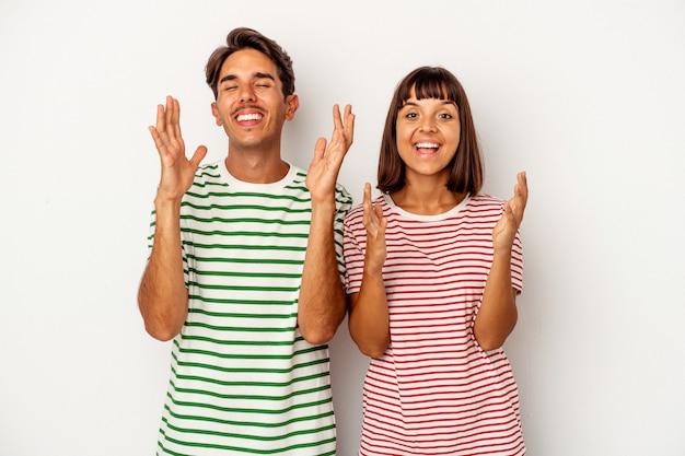 Młoda para rasy mieszanej na białym tle śmieje się głośno trzymając rękę na klatce piersiowej.