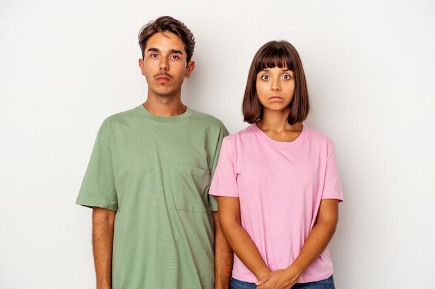 Młoda para rasy mieszanej na białym tle smutna, poważna twarz, uczucie nieszczęśliwego i niezadowolenia.