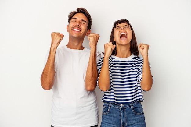 Młoda para rasy mieszanej na białym tle świętuje zwycięstwo, pasję i entuzjazm, szczęśliwy wyraz.