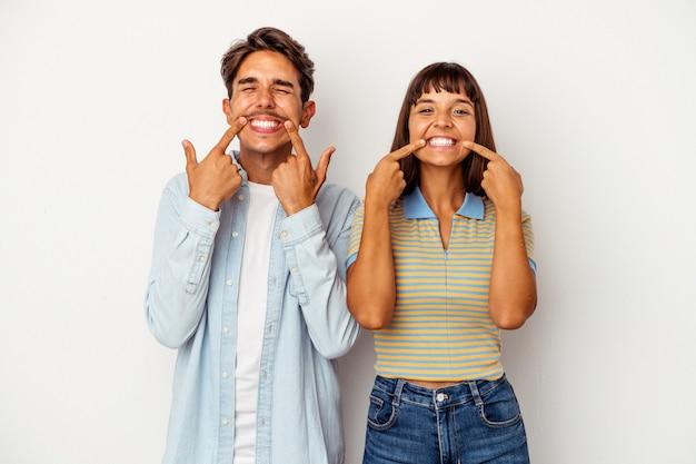 Młoda para rasy mieszanej na białym tle uśmiecha się, wskazując palcami na ustach.
