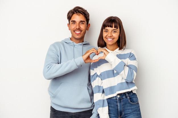 Młoda para rasy mieszanej na białym tle uśmiechając się i pokazując kształt serca rękami.