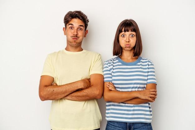 Młoda para rasy mieszanej na białym tle wieje w policzki, ma zmęczony wyraz twarzy. koncepcja wyraz twarzy.