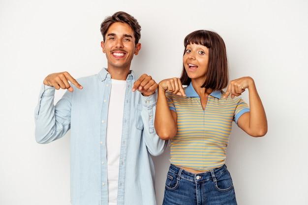 Młoda para rasy mieszanej na białym tle wskazuje palcami w dół, pozytywne uczucie.